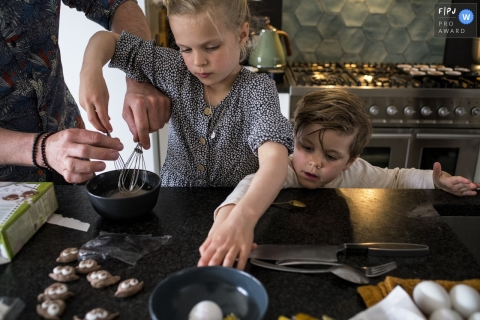 Moment-driven Drenthe family photography of a family cooking in the kitchen with hands reaching