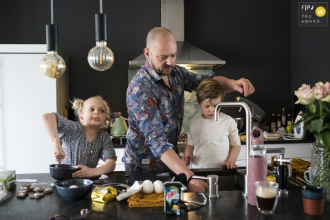 Moment driven Drenthe family photojournalism image of a father and children cooking in the kitchen
