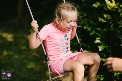 Moment driven Drenthe family photojournalism image of a girl swinging with laughter