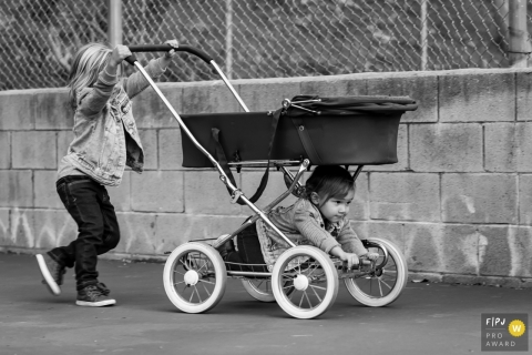 Moment-driven Ventura family photography of an older boy pushing old-school pram with little brother along for the ride