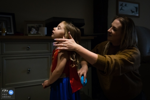 Moment-driven Cambridgeshire family photography captured a Mum brushing the hair of her daughter who is dressed in a superhero outfit which she wears all day long