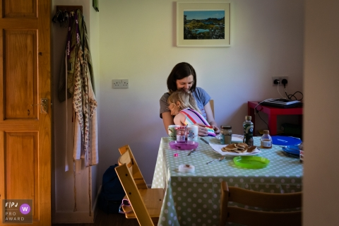 Moment driven Cambridgeshire family photojournalism image capturing Mum and daughter smile whilst having a cuddle at the breakfast table at home