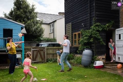 Moment-driven Cambridgeshire family photography showing Mum shoots Dad with a water pistol in the garden while their children look on and laugh