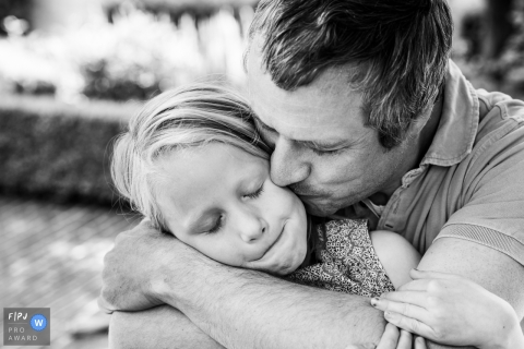Moment-driven Flanders family photography of a dad kiss during BW day in the life session