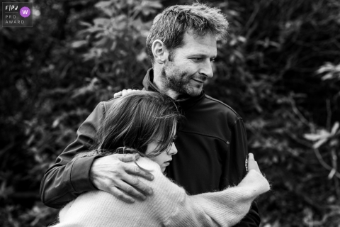 Moment driven Flanders family photojournalism image showing a hug for dad during day in the life session in BW