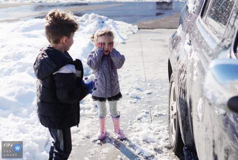 Moment-driven Joplin family photography showing She was not happy that her brother was throwing snow balls at the vehicle