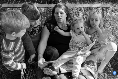 Moment-driven Connecticut family photography showing A mother reads a story to her children in a hammock