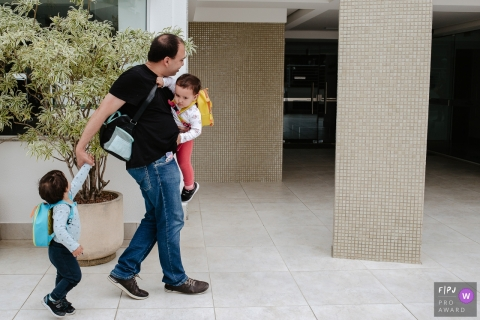 Moment driven Florianopolis family photojournalism image of a Father of twins turning around to be able to take care of them, walking in the condominium of his building, with a son on his lap, backpack and pulling the other son