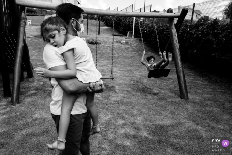 Moment driven Florianopolis family photojournalism image in BW showing a Father with his daughter sleeping on his lap while the other son plays the swing