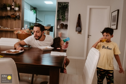 Moment-driven Florianopolis family photography showing a Family having dinner, with father showing his tongue from hunger, son drinking juice and daughter beside him right after eating