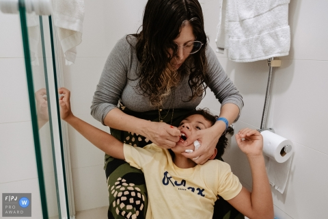 Moment driven Florianopolis family photojournalism image captured the Mother brushing teeth and flossing her son before bedtime in the bathroom at home