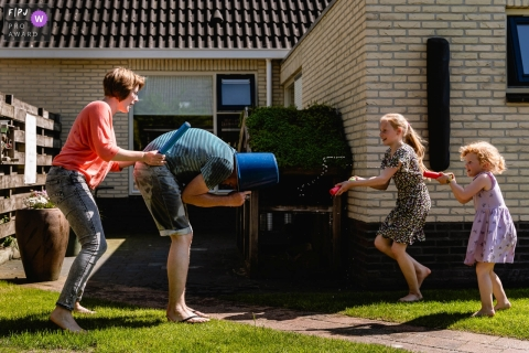 Groningen family fun photography of parents being attacked wth water guns, with father covering his head with a bucket