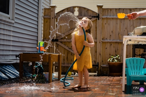 New Hampshire backyard family image of a young girl taking a drink from a garden hose as mom holds a cup out