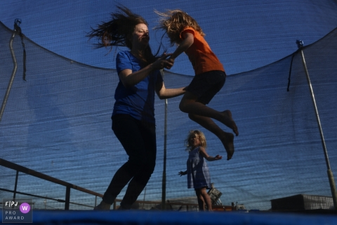 San Francisco family photo session with the mother and kids playing in the trampoline