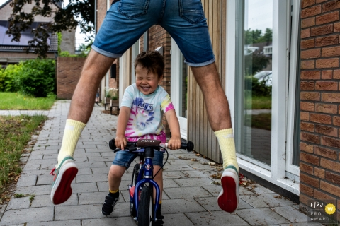 Eindhoven young boy riding his bike through his dad's legs as dad jumps