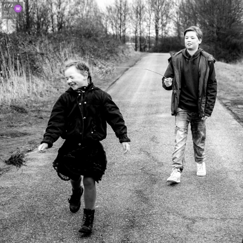Zuid Holland brother and sister take a stroll on a chilly day during a family photo session