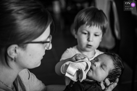 Savoie family photography of a little boy wiping the baby's mouth