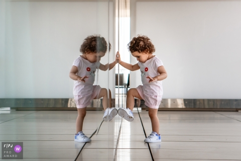 Istanbul family photo of a young girl standing against a mirror and is reflected