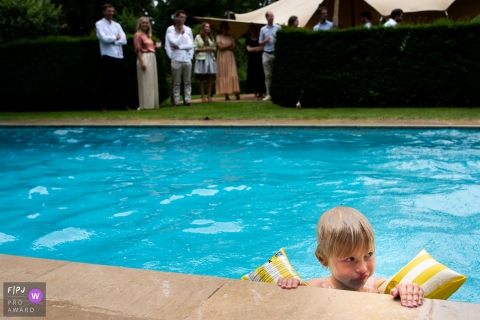East Flanders day in the life photo of a young boy wearing floaties in the backyard pool