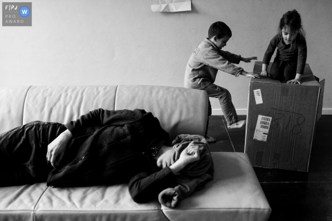 East Flanders day in the life photo of children playing in a box while a resting parent trying to get in a nap