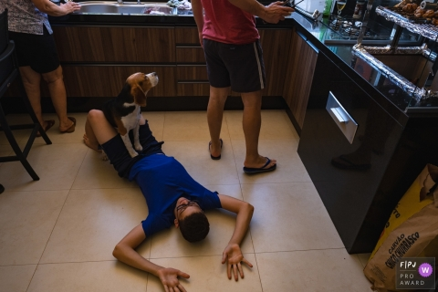 Cuiaba day in the life session with a family working in the kitchen and a dog siting on a boy laying on the floor