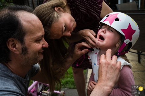 Cambridgeshire family photo showing parents as they comfort their daughter who has hurt her neck while putting her cycling helmet on