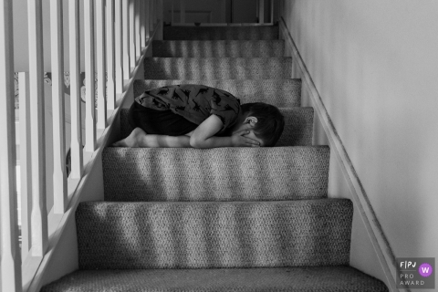 Somerset family photography of boy with his hands on his face laying on a step
