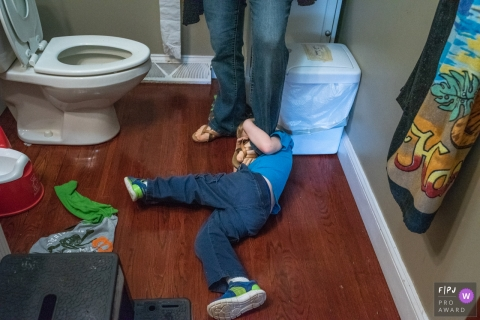Connecticut family image of a young boy struggling with his mother as he lays on the floor in the bathroom