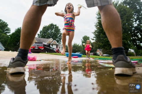 Atlanta Family photographer captures the action of a girl throwing water balloons at her dad