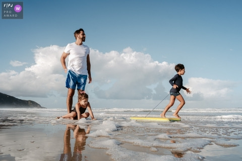 Santa Catarina father and children playing on the beach on a blue sky day during this family photoshoot