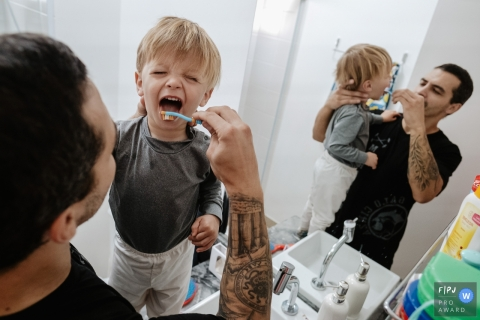 Santa Catarina father brushing his son's teeth in front of the bathroom mirror during an at-home photo session