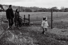 Little girl walking across the fields with her brother and parents strolling in the background