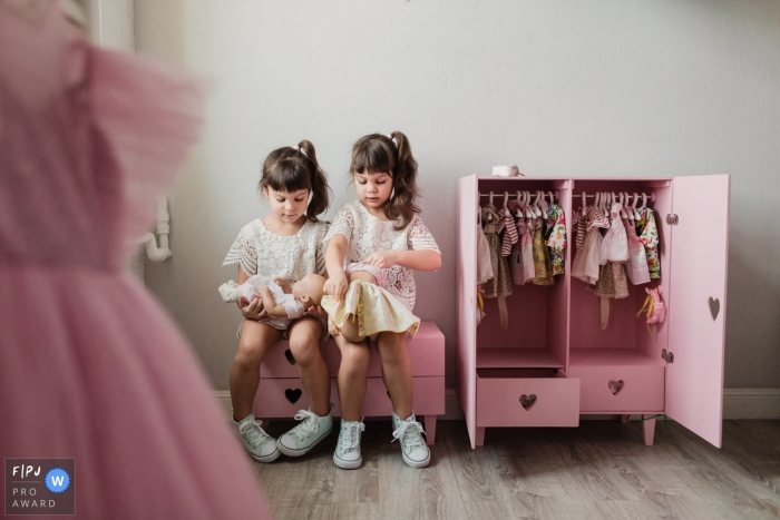 Two identically dressed girls play with dolls in their room in this photo captured by a Saint-Petersburg family documentary photographer.