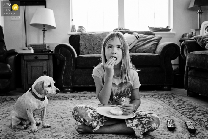A young girl enjoys a snack on the floor during a movie while her dog patiently waits for a bite in this photo captured by a Key West family photojournalist