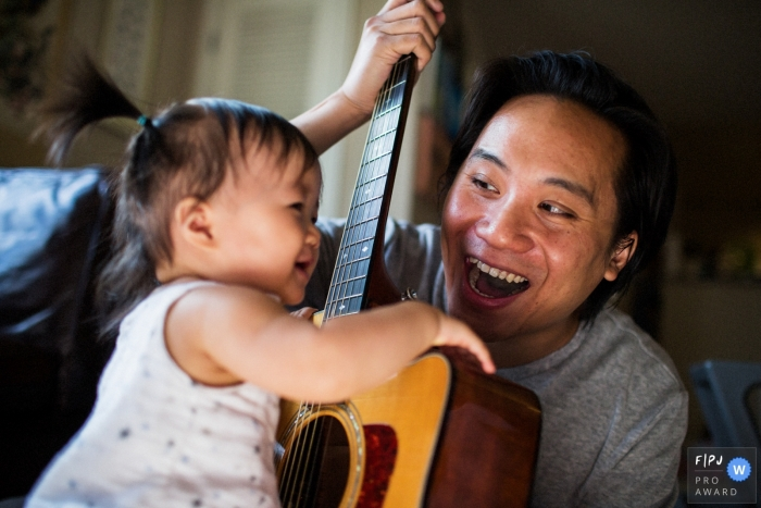 San Francisco family photojournalist captured this photo of a father helping his toddler daughter strum an acoustic guitar