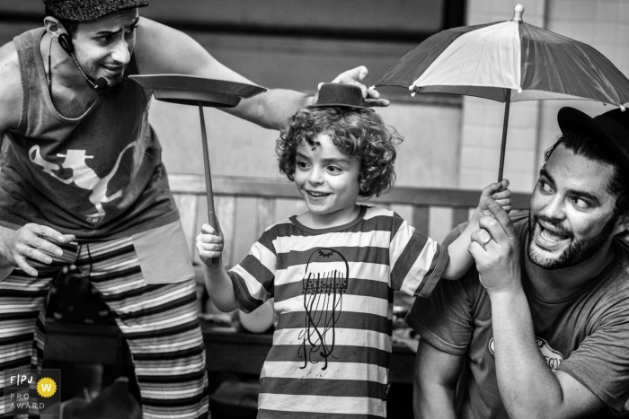 Rio de Janeiro family photojournalist captures this black and white image of a young boy showing performing fun tricks with his family