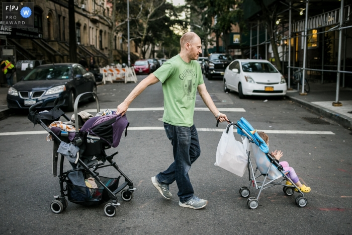 A father shows off is stroller steering skills as he navigates two across a street in this photo captured by a Brooklyn documentary family photographer