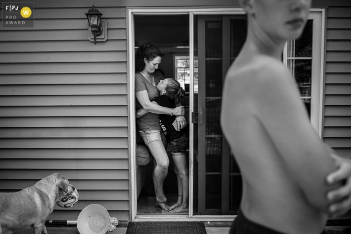 Brooklyn family photojournalist captured this black and white photo of a mom and daughter embracing in the doorway as the family dog waits for someone to throw her a ball