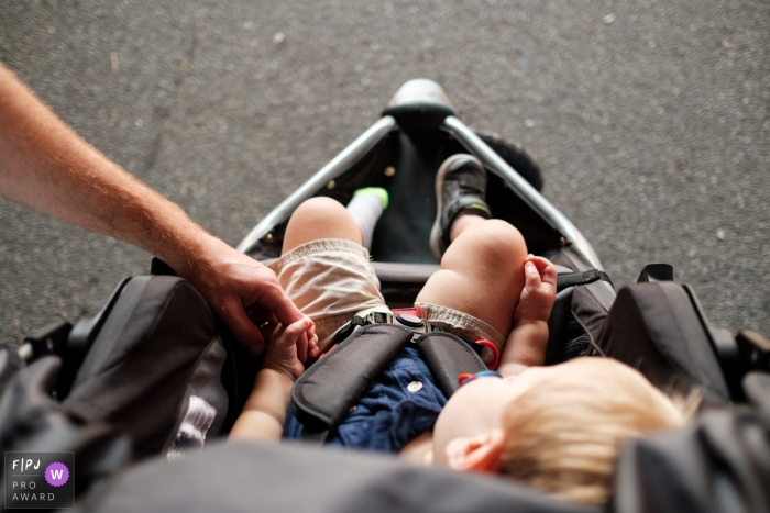 This image of a toddler asleep in a stroller while grasping his father's hand was captured by an Atlanta family photojournalist