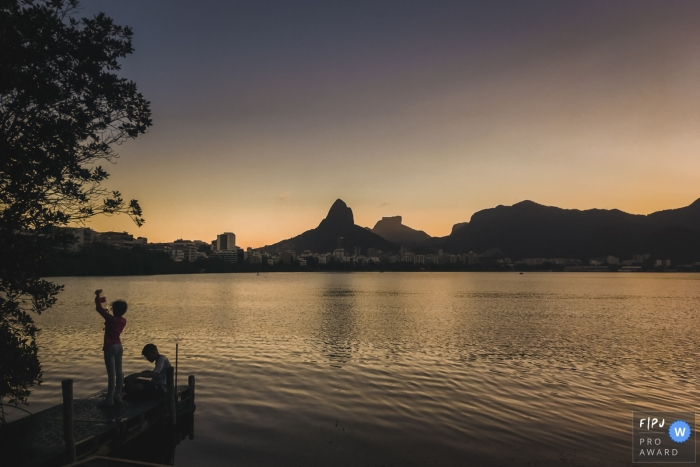 Family photo of two people sitting on a dock in front of a lake surrounded by mountains by a Rio de Janeiro, Brazil family photojournalist.