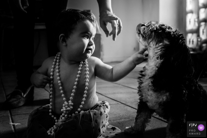 A little girl wears a large pearl necklace while she pets her dog in this image created by a Landes family photographer.