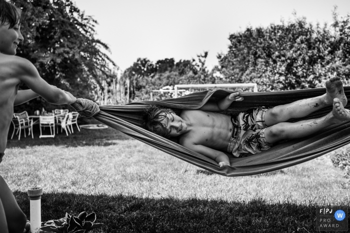 A boy swings his brother in a hammock in this picture captured by a Copenhagen, Denmark family photojournalist.