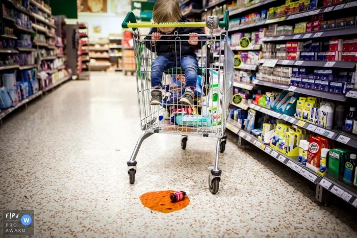 Un petit garçon dans un chariot d'épicerie baisse les yeux sur une bouteille cassée sur cette photo enregistrée par un photographe de famille de style documentaire primé par Bath, Somerset.
