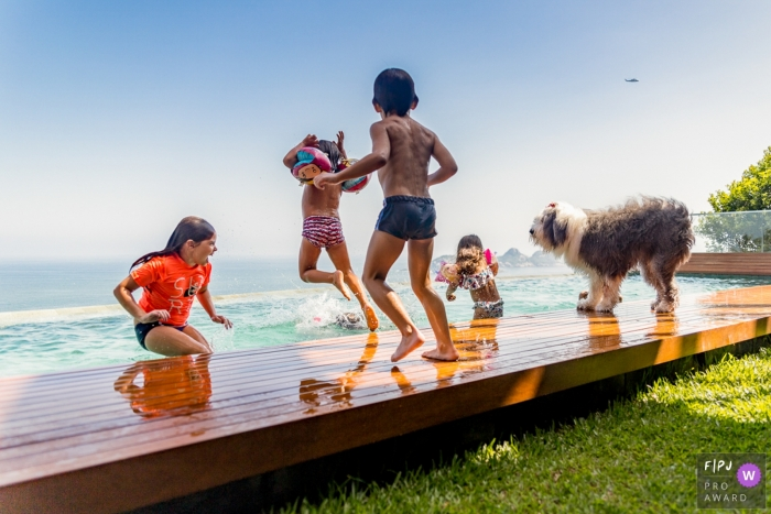 Four children play on a dock by the ocean with their dog in this Family Photojournalist Association contest awarded photo created by a Sao Paulo, Brazil family photographer.