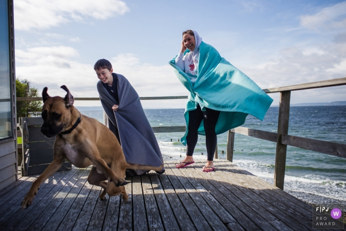 A mother and son wearing blankets wrapped around them on a windy beach day laugh as their dog runs across their porch in this photograph created by a San Francisco, CA family photojournalist.