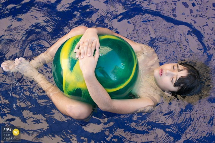 A boy holds a large ball against his stomach as he floats on his back in a pool in this photo by a Minas Gerais award-winning family photographer.