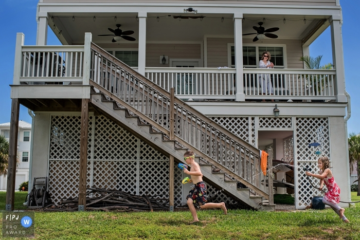 A girl chases her brother with a hose outside  in this picture captured by a Key West, FL family photojournalist.