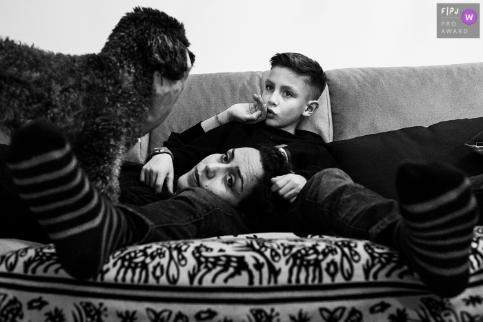 A mother lays on her son's lap as she pets the family dog in this family picture by an Antwerpen photographer.