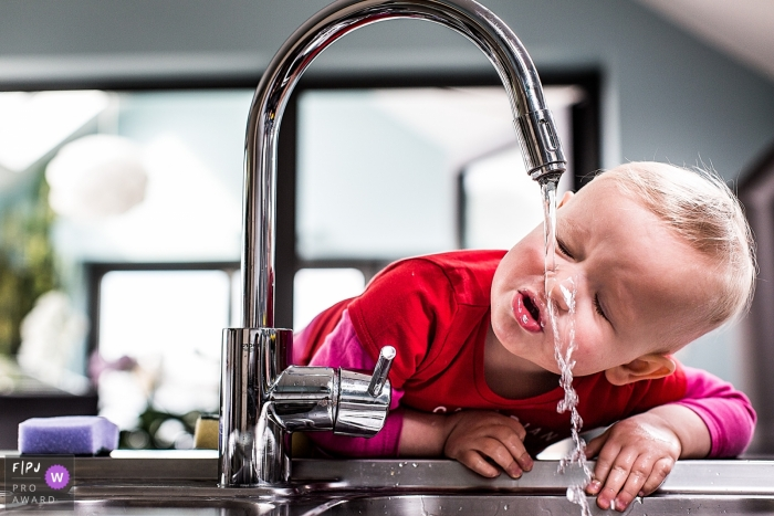 A little boy tries to drink from the kitchen faucet in this FPJA award-winning picture by an Antwerpen family photographer.