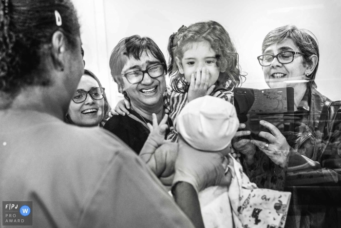 A nurse holds up a newborn baby for its family to see in the hospital in this black and white photo by a Rio de Janeiro, Brazil documentary birth photographer.